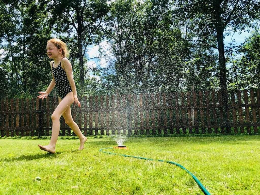 Young girl playing in the sprinkler on the lawn