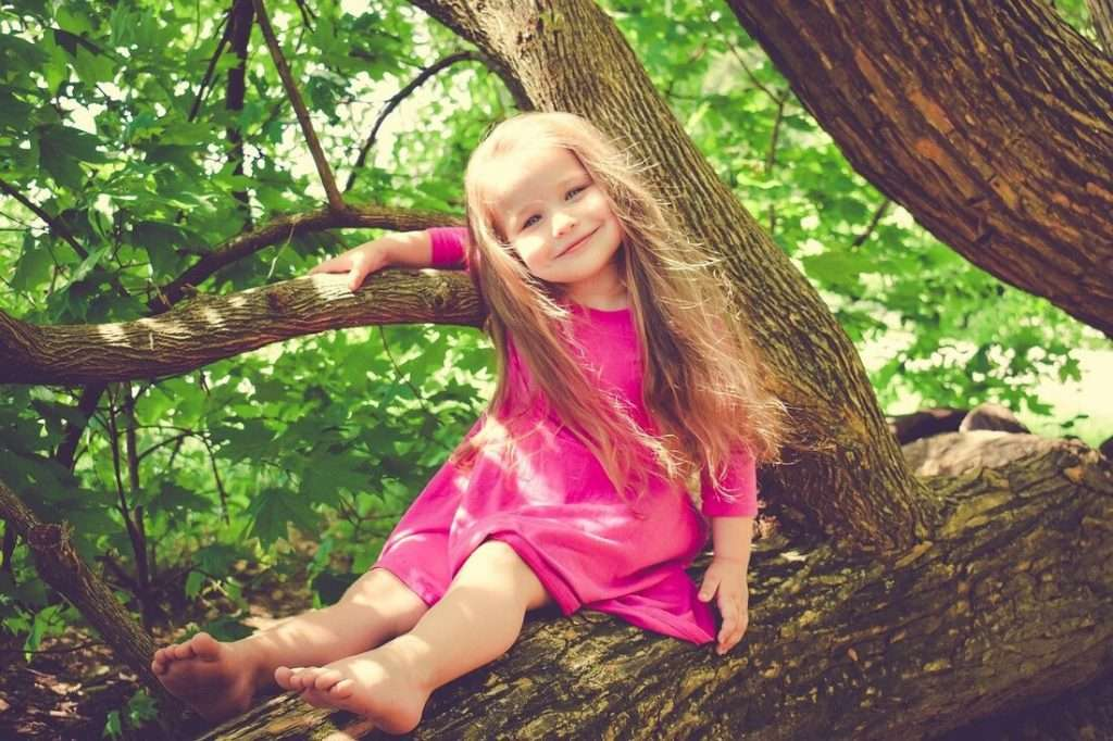Young girl in a pink dress sitting in the tree.